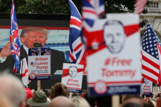 Demonstrators-hold-placards-supporting-EDL-founder-Tommy-Robinson-and-US-President-Donald-Trump-in